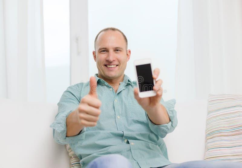 Glimlachende mens met smartphone thuis stock afbeeldingen