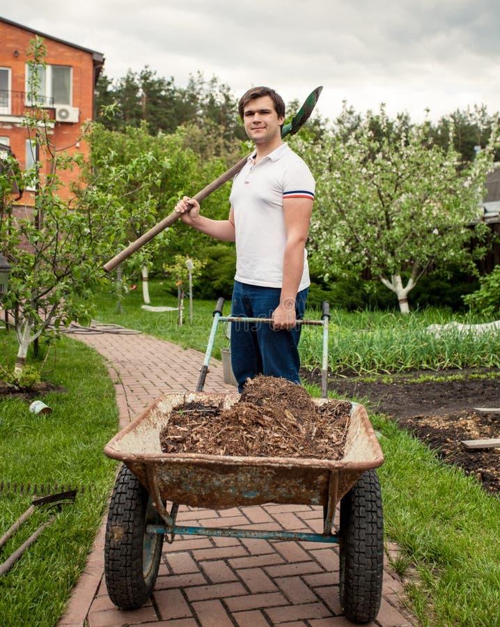 Glimlachende mens met spade en tuinkruiwagen stock afbeelding