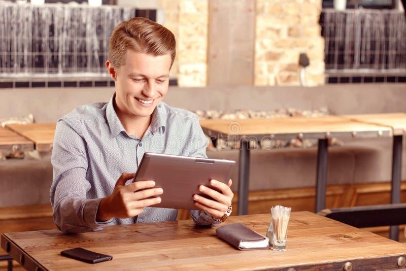 Glimlachende mens met tablet in koffie stock fotografie