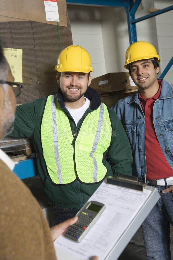Glimlachende Mensen die Bouwvakkers in Fabriek dragen stock foto