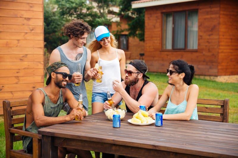 Glimlachende mensen die en bier in openlucht spreken drinken bij de lijst stock afbeelding