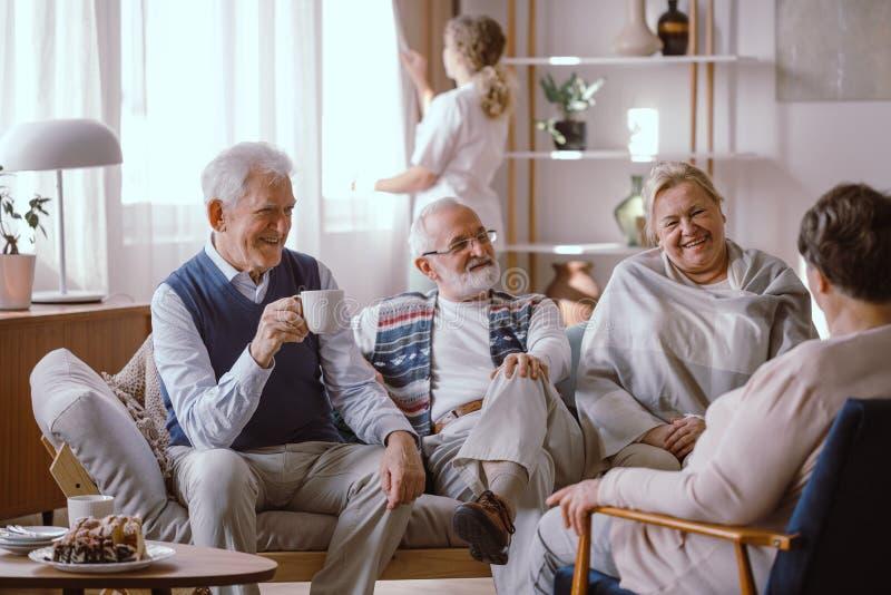 Glimlachende mensen die samen in verpleeghuis spreken stock fotografie