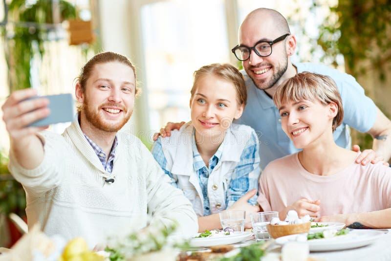 Glimlachende mensen die selfie in restaurant nemen stock afbeelding