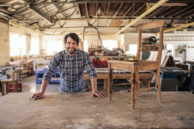 Glimlachende meubilairmaker die een stoel op zijn werkbank schuren royalty-vrije stock foto