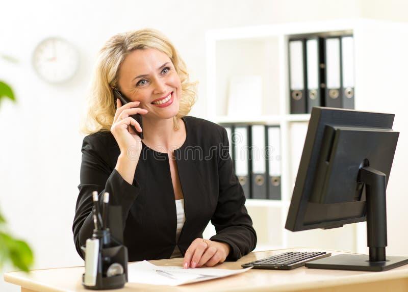 Glimlachende midden oude beambte die op celtelefoon spreken in bureau stock afbeeldingen