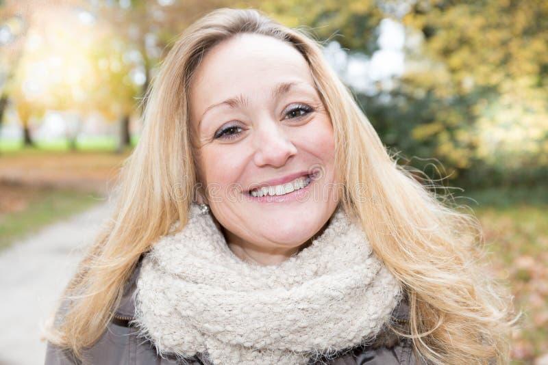 glimlachende midden oude blondevrouw in openlucht in de herfst royalty-vrije stock fotografie