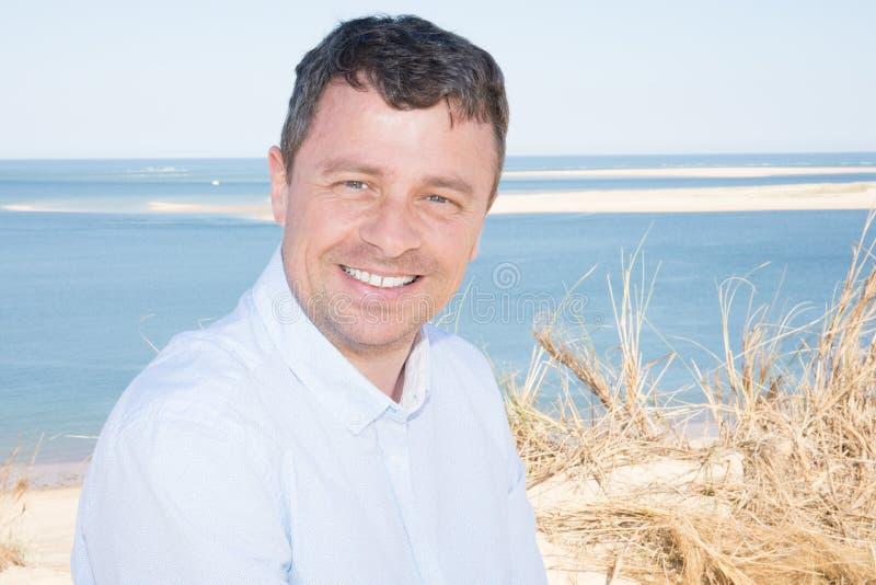 Glimlachende midden oude mens die op overzeese strandkust in de zomervakantie glimlachen royalty-vrije stock foto