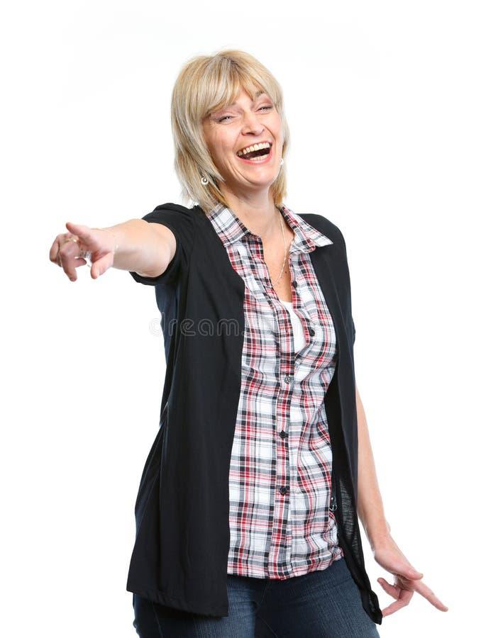Glimlachende middenleeftijdsvrouw die op u richt stock fotografie