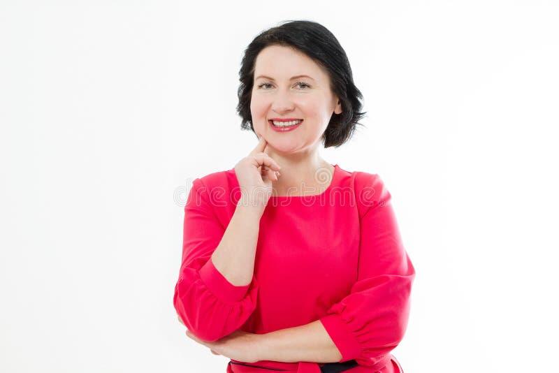 Glimlachende Middenleeftijdsvrouw met witte gezonde tanden in rode kleding en gekruiste die wapens op witte achtergrond wordt geï royalty-vrije stock foto's