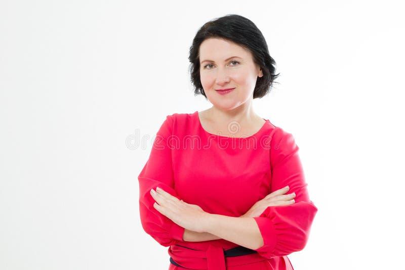 Glimlachende Middenleeftijdsvrouw in rode kleding en gekruiste die wapens op witte achtergrond wordt geïsoleerd Maak omhoog en sc royalty-vrije stock afbeeldingen