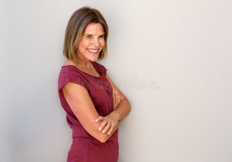 Glimlachende middenleeftijdsvrouw tegen witte muur royalty-vrije stock foto's