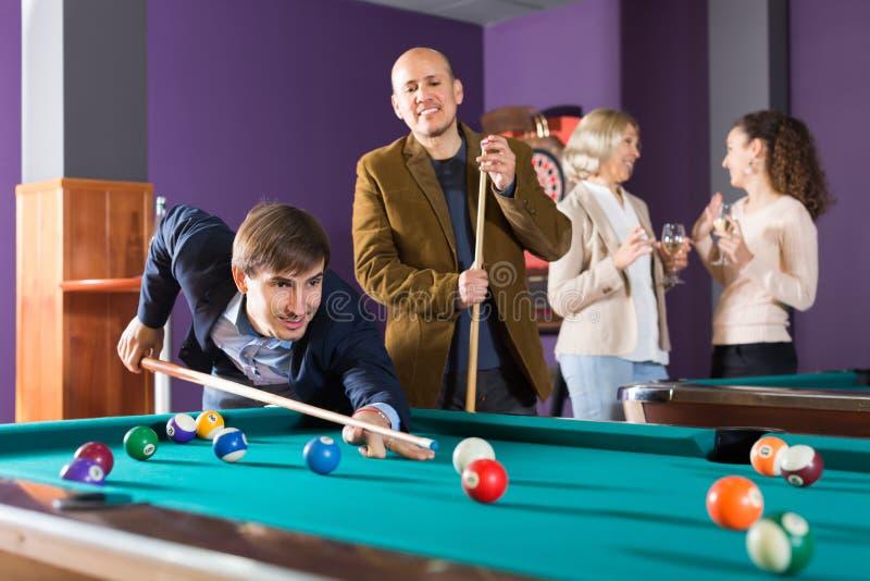 Glimlachende middenstandmensen die poolspel hebben stock foto's