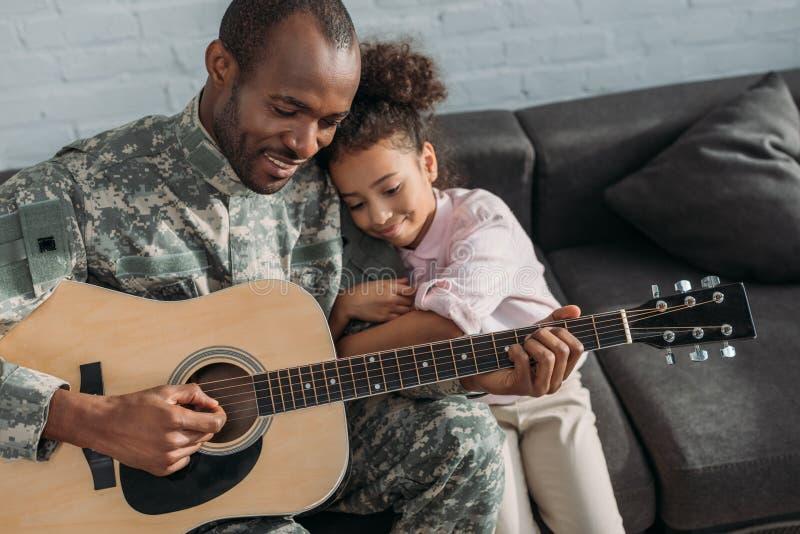 Glimlachende militair het spelen gitaar stock foto