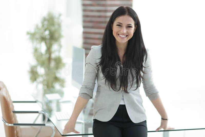 Glimlachende moderne bedrijfsvrouw die zich dichtbij een het werklijst bevinden royalty-vrije stock afbeelding