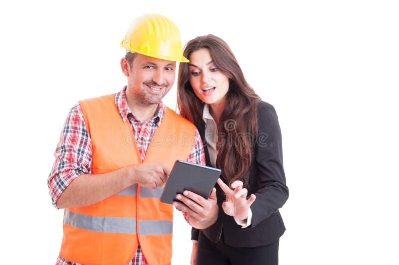 Glimlachende moderne bouwer en bedrijfsvrouw die draadloze tablet gebruiken royalty-vrije stock afbeeldingen