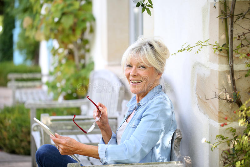 Glimlachende moderne hogere vrouw die in openlucht tablet gebruiken stock afbeeldingen