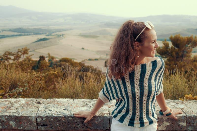 Glimlachende moderne toeristenvrouw die afstand onderzoeken royalty-vrije stock foto