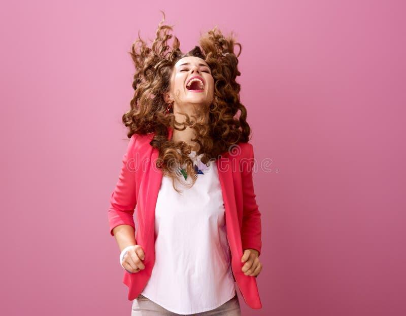 Glimlachende modieuze die vrouw op roze het schudden haar wordt geïsoleerd royalty-vrije stock fotografie