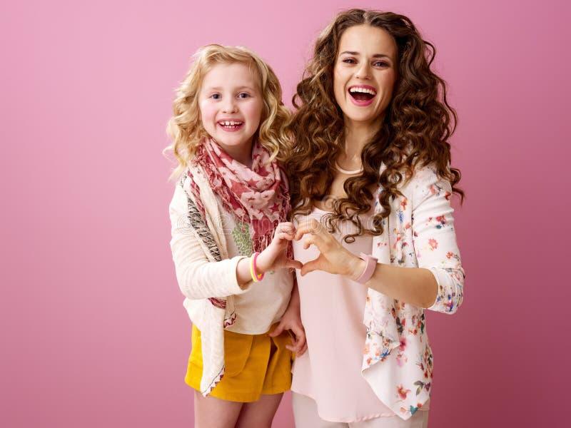 Glimlachende modieuze moeder en dochter die hart gevormde handen tonen royalty-vrije stock afbeeldingen