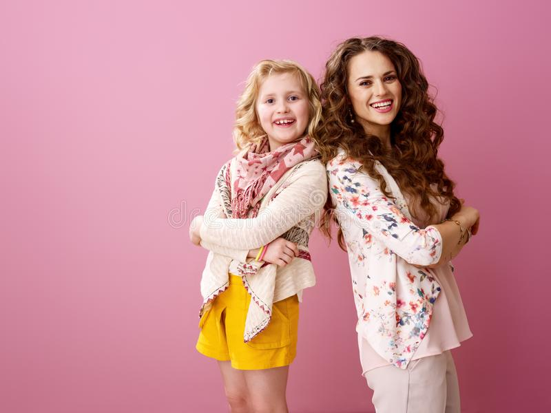 Glimlachende modieuze moeder en dochter op roze achtergrond royalty-vrije stock foto's