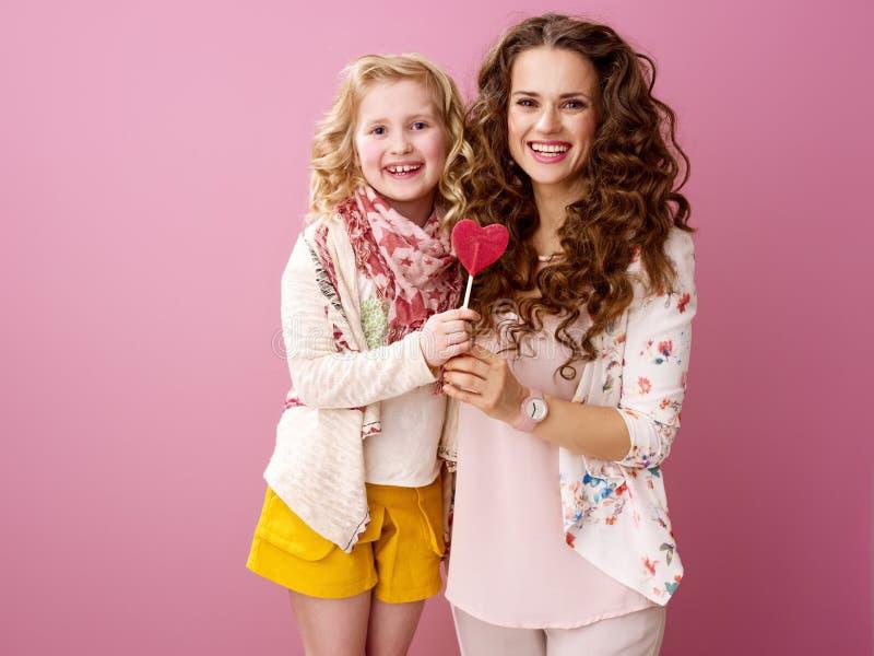Glimlachende modieuze moeder en kindholdingshart gevormde lolly royalty-vrije stock foto's