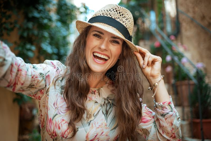 Glimlachende modieuze toeristenvrouw in de oude stad die van Europa selfie nemen stock afbeelding