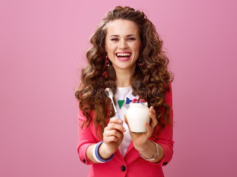 Glimlachende modieuze vrouw die landbouwbedrijf organische yoghurt en lepel tonen stock afbeeldingen