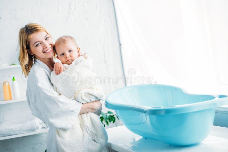 glimlachende moeder in badjas die aanbiddelijk kind vervoeren royalty-vrije stock afbeeldingen