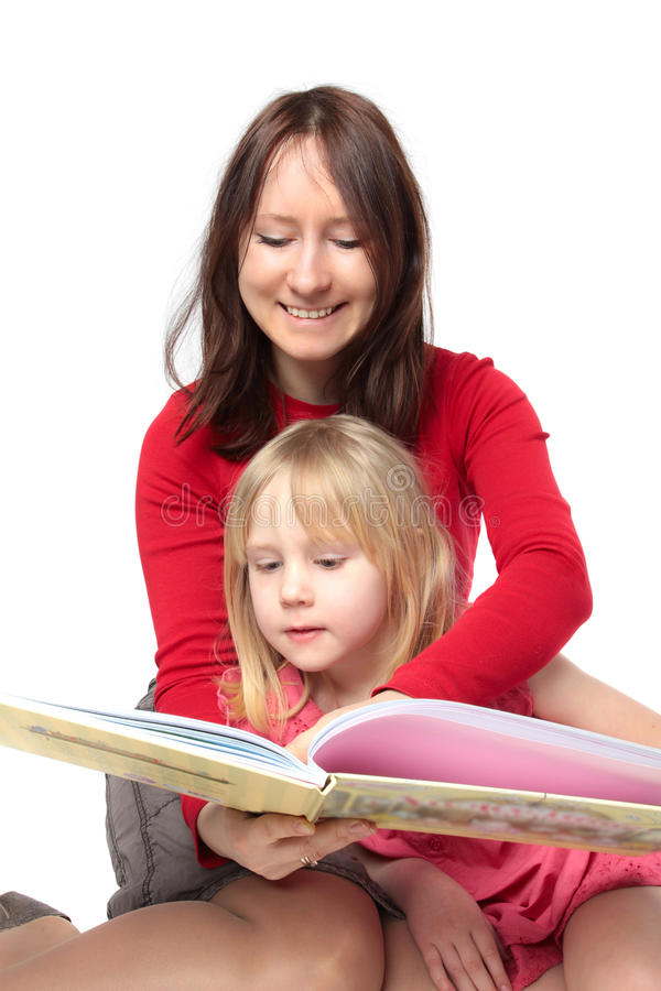 Glimlachende moeder die een boek met kind leest stock afbeeldingen