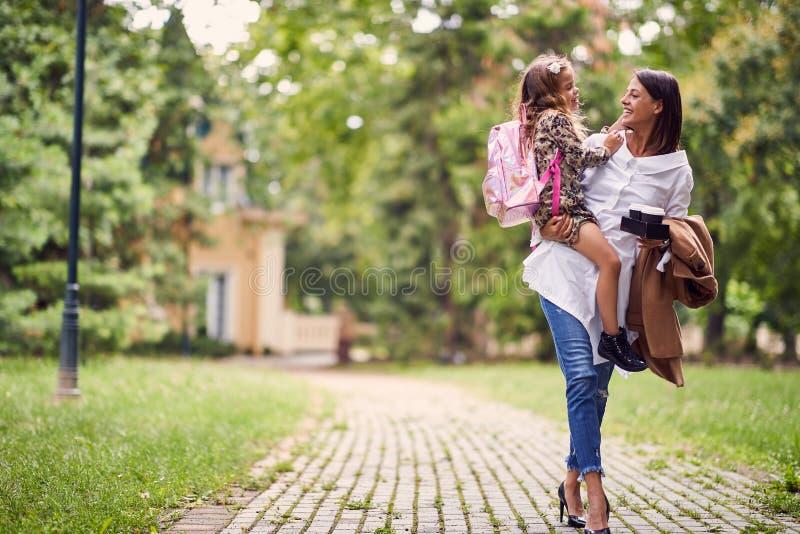 Glimlachende moeder die een dochter met schooltas houden royalty-vrije stock foto