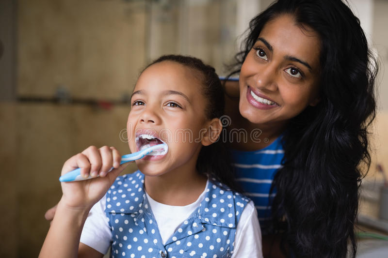 Glimlachende moeder die zich door dochter het borstelen tanden in badkamers bevinden royalty-vrije stock foto