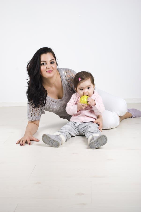 Glimlachende moeder en babymeisjeszitting op vloer royalty-vrije stock fotografie