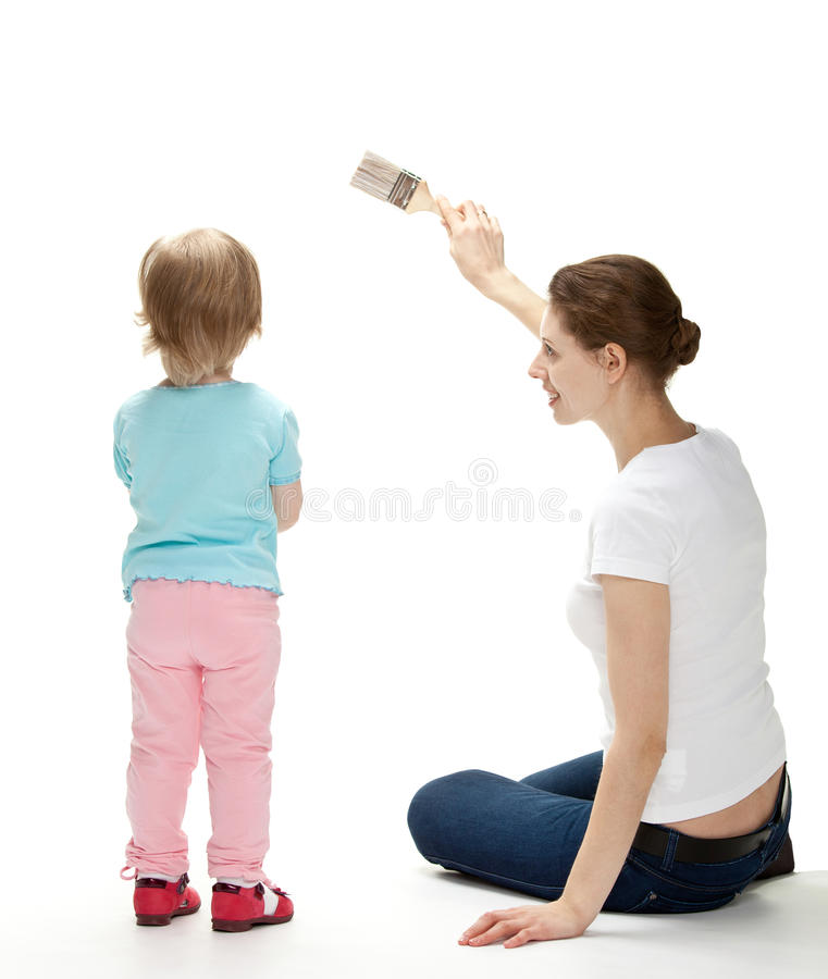 Glimlachende moeder en dochter die de muur schilderen stock fotografie