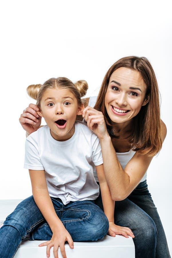 Glimlachende moeder en dochter die pret hebben samen en camera bekijken stock afbeelding