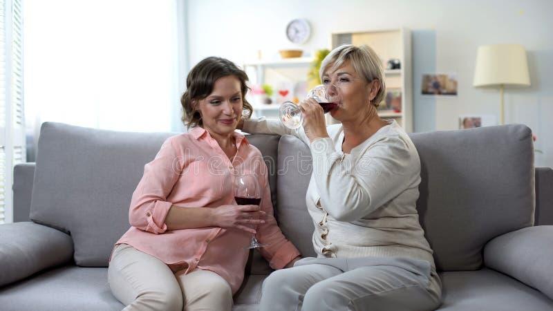 Glimlachende moeder en dochter het babbelen het drinken wijn thuis, tedere relaties royalty-vrije stock afbeeldingen