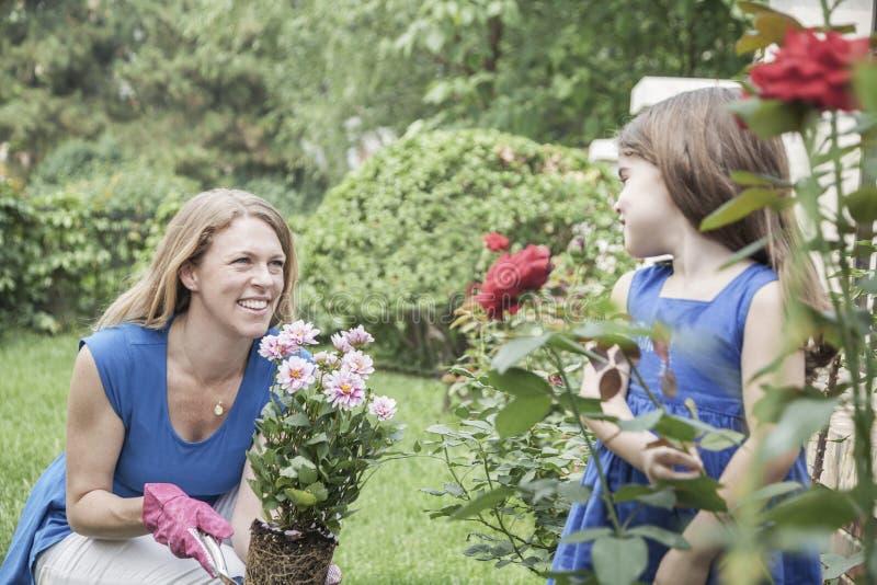 Glimlachende moeder en dochter het tuinieren bloemen in de tuin stock afbeelding