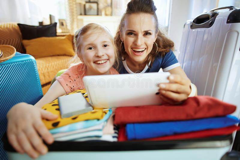 Glimlachende moeder en dochtertoeristen die vluchten online kopen royalty-vrije stock foto's