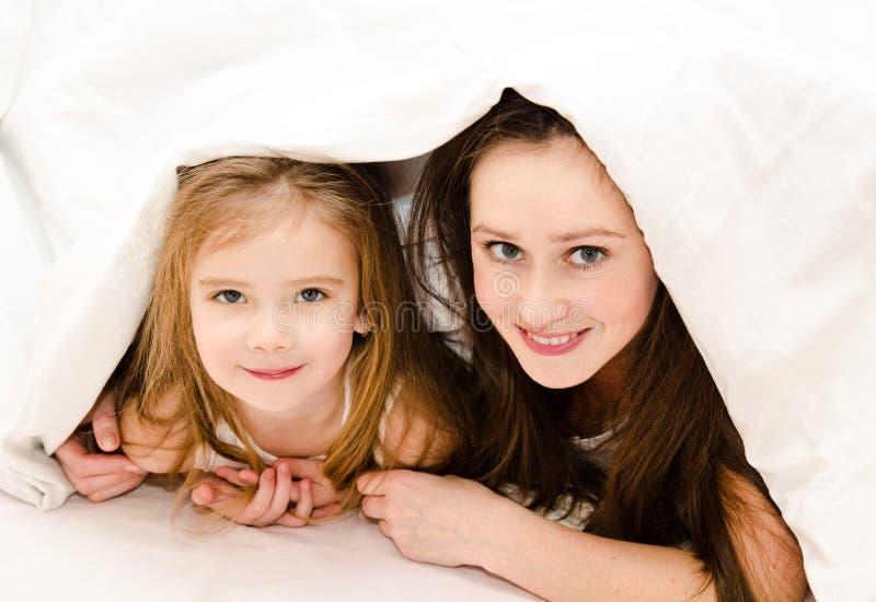 Glimlachende moeder en haar meisje die samen op een bed spelen royalty-vrije stock foto's