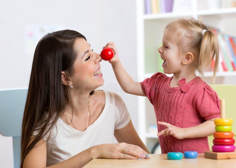 Glimlachende moeder en kinddochter in het kinderdagverblijf, de gelukkige tijd en de samenhorigheid stock foto's