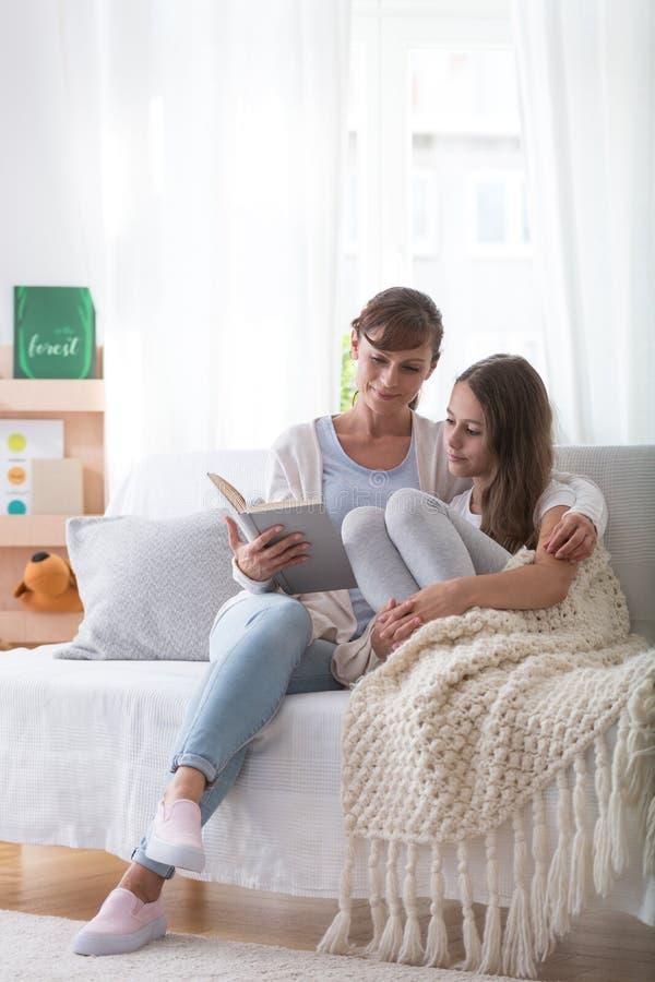 Glimlachende moeder en tienerdochterzitting op de laag, lezingsboek samen royalty-vrije stock afbeeldingen
