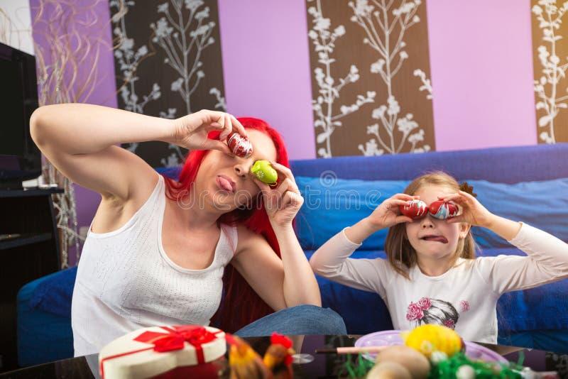 Glimlachende moeder en vrolijk dochter samen speels paasei royalty-vrije stock afbeeldingen
