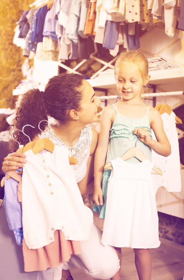 Glimlachende moeder met dochter het kopen babypyjama's in jonge geitjessectie stock fotografie