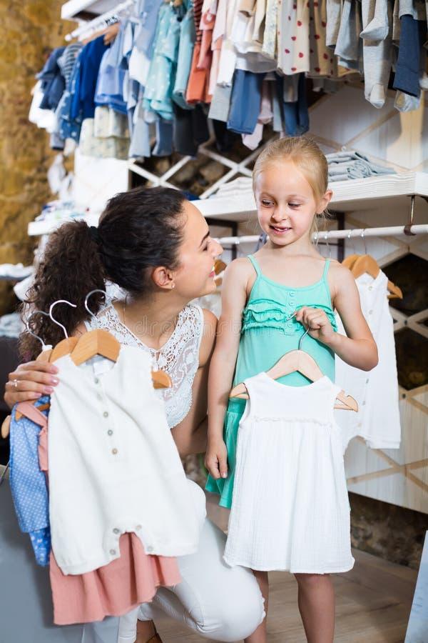Glimlachende moeder met dochter het kopen babypyjama's in jonge geitjessectie stock afbeeldingen