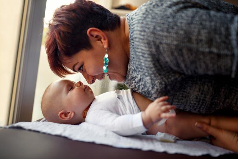 Glimlachende moeder met haar baby genietende van en speelfamilie happin stock afbeelding