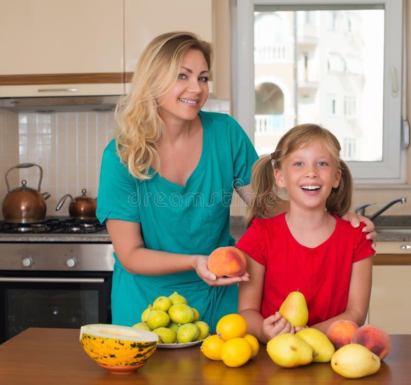 Glimlachende moeder met het houden van zoete perendochter Het gezonde eten - vrouw en kind in de keuken met verschillende soorten royalty-vrije stock afbeeldingen