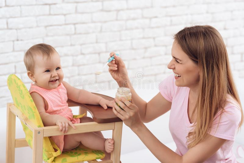 Glimlachende moeder met puree voedende glimlachende baby stock afbeeldingen