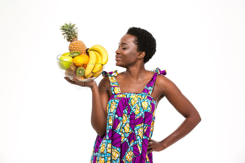Glimlachende mooie Afrikaanse vrouw die en zich met exotische vruchten bevinden stellen royalty-vrije stock fotografie
