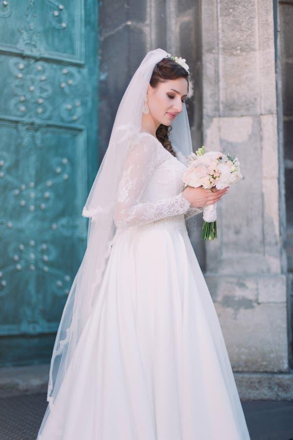 Glimlachende mooie bruid op uw huwelijksdag met groot boeket dichtbij kerk Groene oude deur stock afbeeldingen