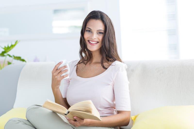 Glimlachende mooie donkerbruine holdingsmok en lezing een boek terwijl het ontspannen op de laag stock afbeeldingen