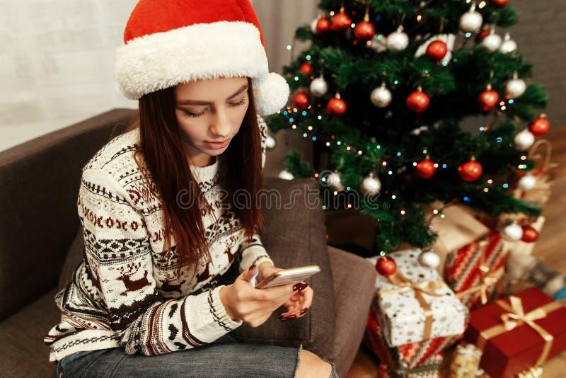 Glimlachende, mooie donkerbruine vrouw in de rode hoed van de Kerstman en whi stock afbeelding